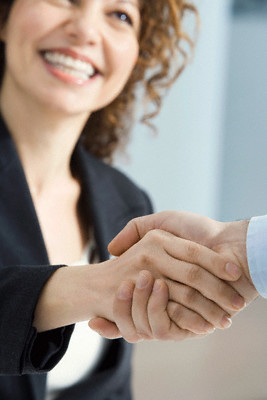 Businesswoman smiles and shakes hands