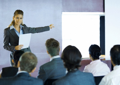 Executives Sitting in Seminar, Woman Standing Facing Group, Gesturing to Screen